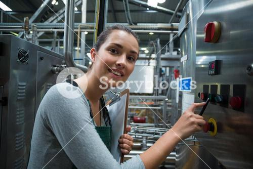 Female factory worker operating machine