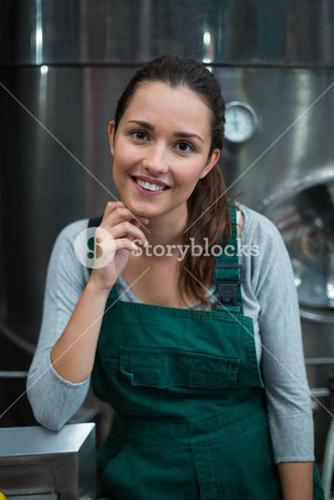 Female factory worker standing at drinks production factory