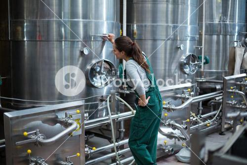 Female factory worker looking at control wheel of storage tank