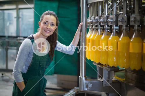 Female factory worker standing near production line
