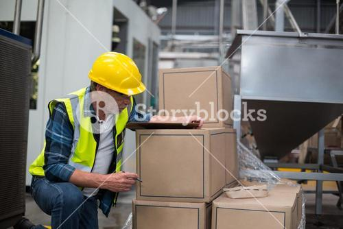 Male factory worker counting cardboard boxes