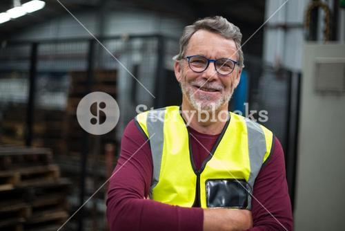 Portrait of male factory worker standing with arms crossed