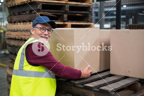 Factory worker loading cardboard boxes on trolley