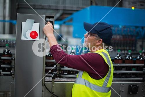 Factory worker operating machine