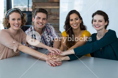 Group of smiling business executives forming hand stack in office