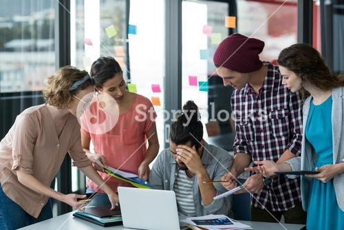 Colleagues with digital tablet and mobile phone talking to frustrated man
