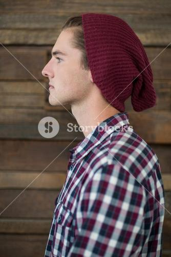 Side view of business executive standing against wooden wall