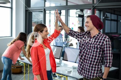 Business executives giving high five in office