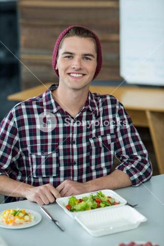 Smiling business executive having meal in office