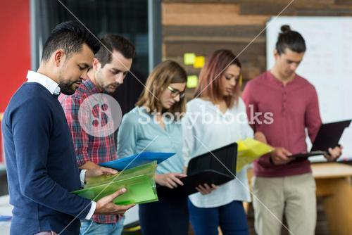 Business executives looking over file in office