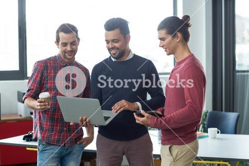 Businesspeople having discussion over laptop