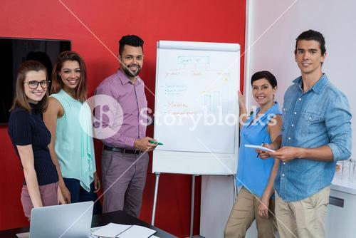Portrait of smiling business executives discussing over flip chart during meeting