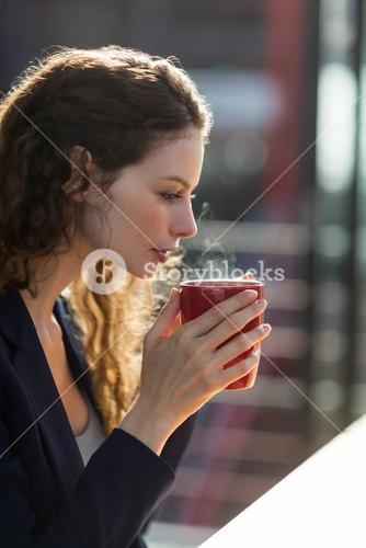 Businesswoman drinking cup of coffee in office