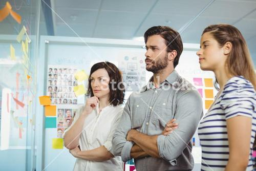 Team of business executives looking at sticky notes