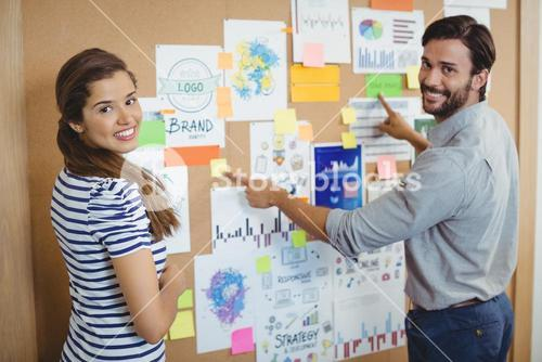 Portrait of two business executives discussing over bulletin board
