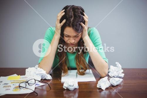 Frustrated female business executive sitting with crumpled papers balls
