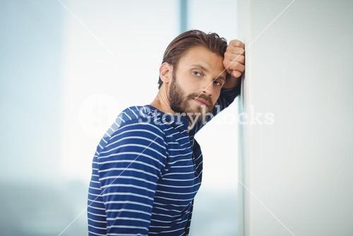 Portrait of sad business executive leaning on wall