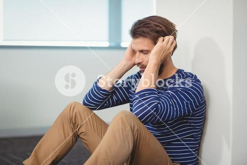Sad business executive sitting against wall