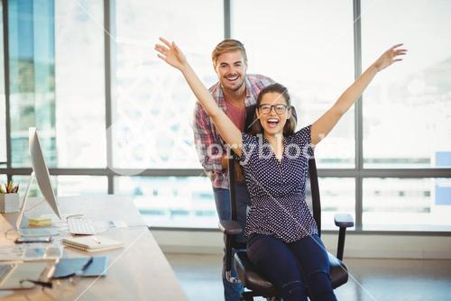Playful man pushing his colleague on office chair