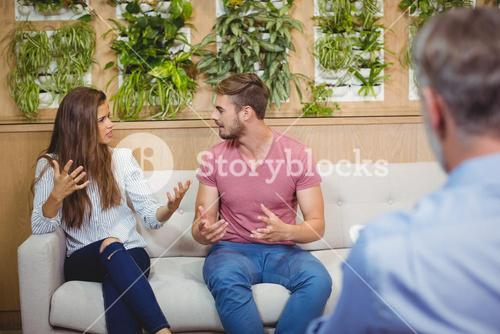 Couple arguing in counselling session with a doctor