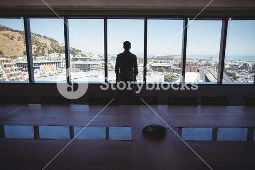 Male business executive looking through window