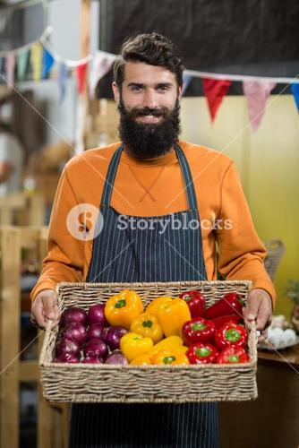 Vendor holding a basket of onion and capsicum at the grocery store