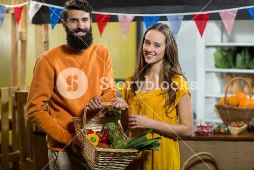 Man and woman holding a basket of vegetables at the grocery store