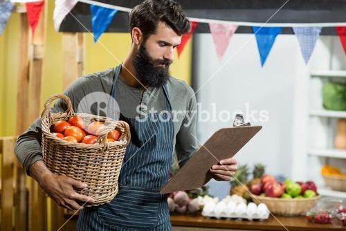 Vendor holding a clipboard and a basket of tomatoes
