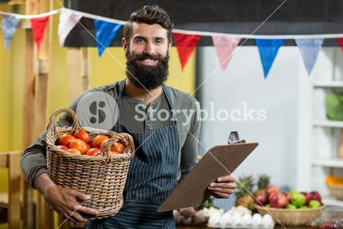 Vendor holding a clipboard and a basket of tomatoes at the grocery store