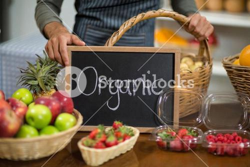 Worker holding a board with organic sign at grocery store