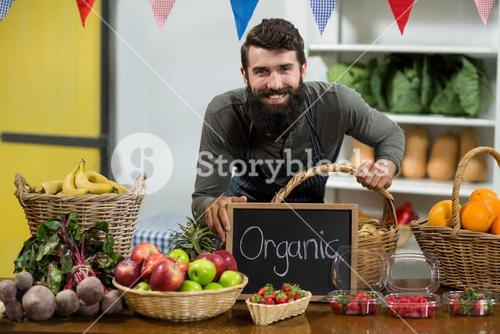 Smiling worker holding a board with organic sign at grocery store