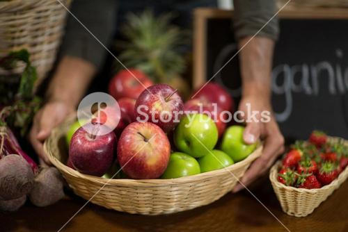 Vendor holding a basket of apples at the grocery store