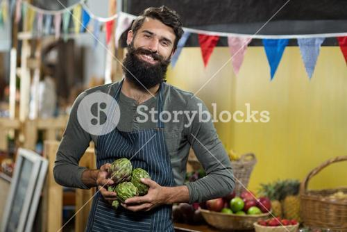 Vendor holding custard apples at the grocery store