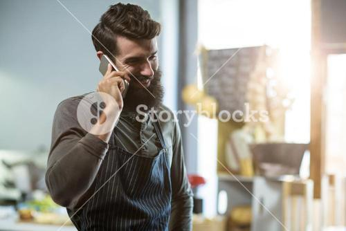 Salesman talking on mobile phone at counter