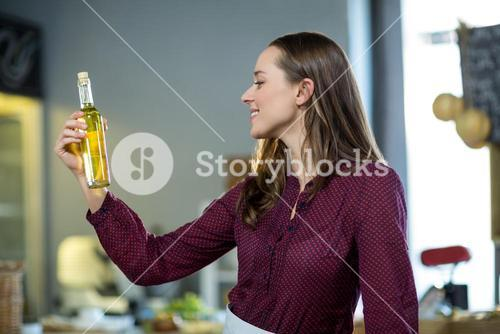 Shop assistant looking at olive oil bottle