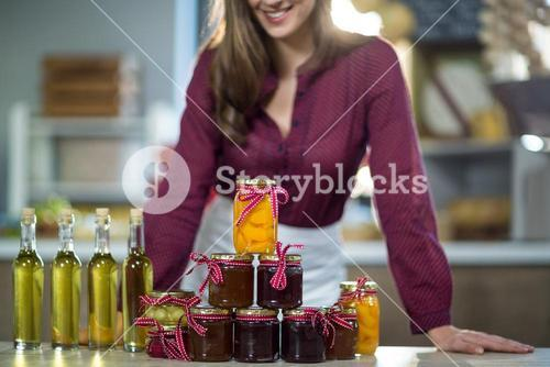 Olive oil, jam, pickle placed together on table