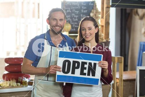 Portrait of smiling bakery staff holding board with open sign at counter