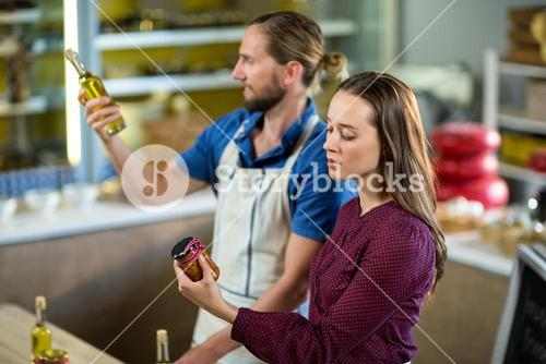 Shop assistants looking at olive oil and pickle bottles