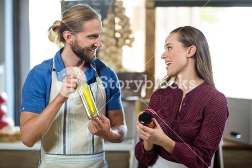 Shop assistants interacting while holding olive oil and pickle bottles