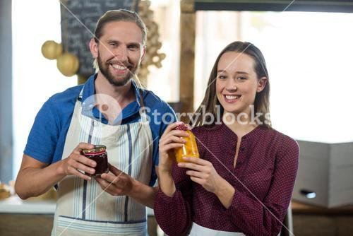 Shop assistants interacting while holding jam and pickle jar at grocery shop
