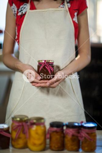Female shop assistant holding a jar of jam
