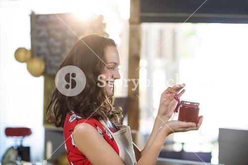 Female shop assistant looking a jar of jam