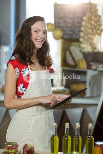 Female shop assistant using digital tablet at the counter in grocery shop