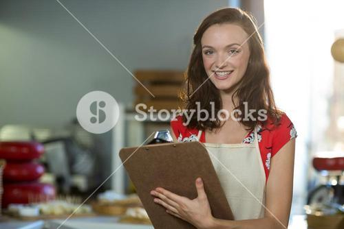 Female shop assistant writing on the clipboard at the counter