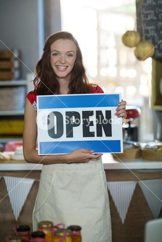 Female shop assistant holding open sign board