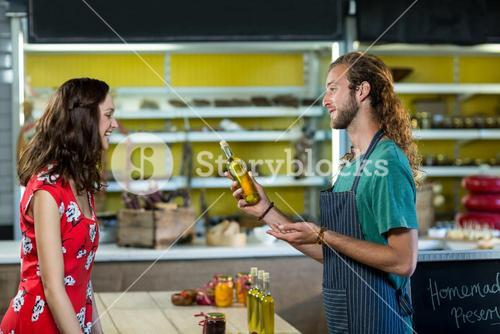 Shop assistant offering olive oil bottle to the customer