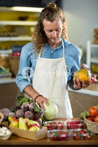 Vendor holding fruits at the counter