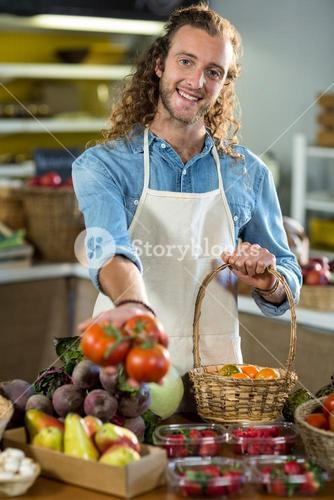 Smiling vendor offering tomatoes in the grocery store
