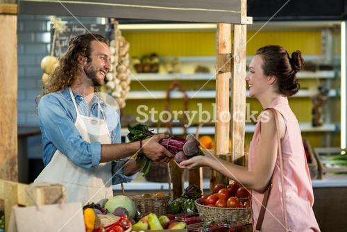 Vendor giving beetroot to the woman at the counter