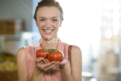 Woman holding tomatoes in grocery store